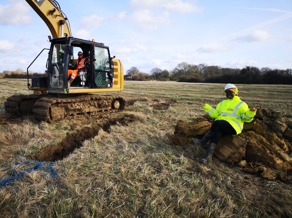 woman wearing hi vis vest and hard hat sitting in field next to digger