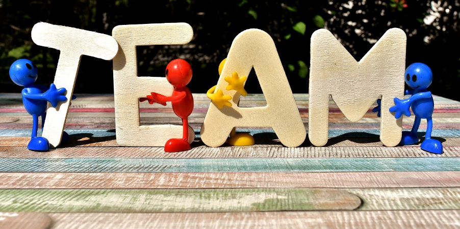 'TEAM' spelt out in wooden letters with mini people figurines holding the letters